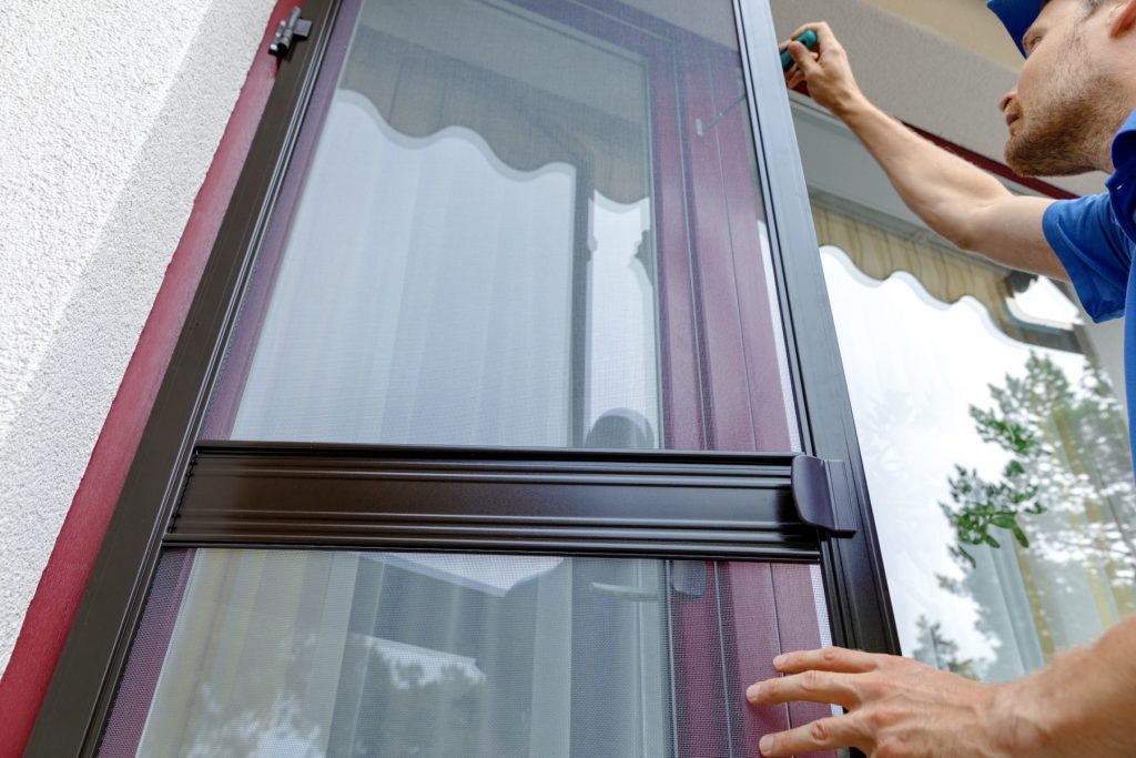 professional installing a security screen in a house